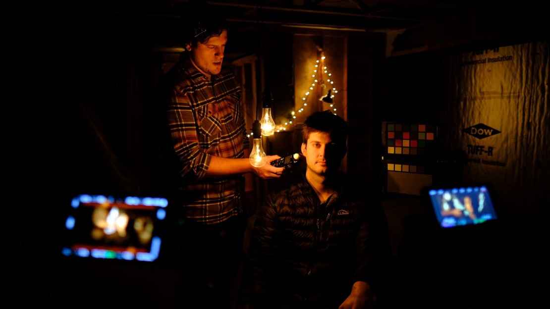 DP Justin Derry takes a light meter reading on set, as Frank Appolonio sits in.
