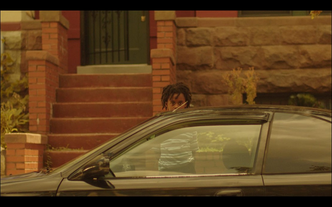 A young child stands across the street in a DC neighborhood featured in 'Residue.'