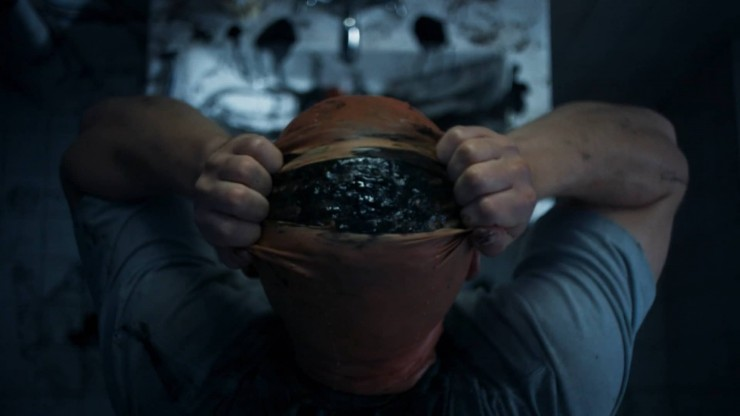 Still of man rippping mysterious black stuff our of scalp